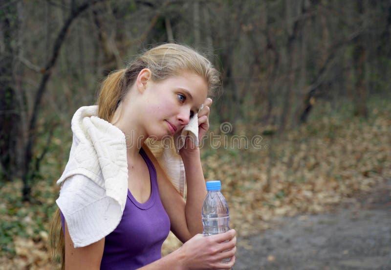 De vrouwenagent stoot op bosweg in park aan stock afbeeldingen