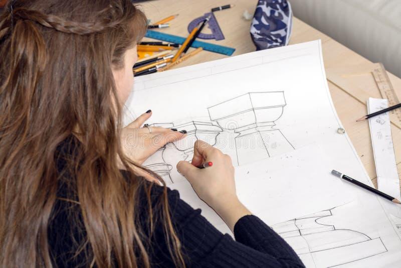 De vrouwenarchitect trekt een plan, ontwerp, geometrische vormen door potlood op groot blad van document bij bureau royalty-vrije stock afbeeldingen