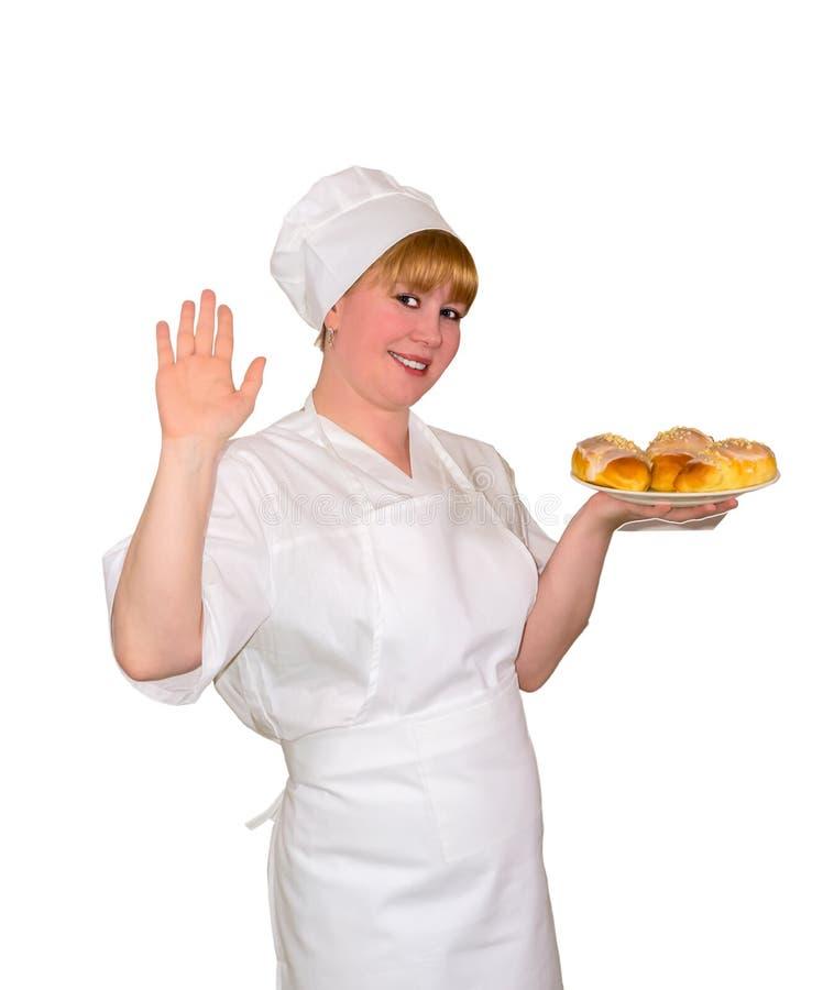 De vrouwenbakker houdt een schotel met zoete geïsoleerde broodjes royalty-vrije stock foto