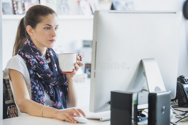 De vrouwenberoeps gebruikt een computer drinkend een drank royalty-vrije stock fotografie