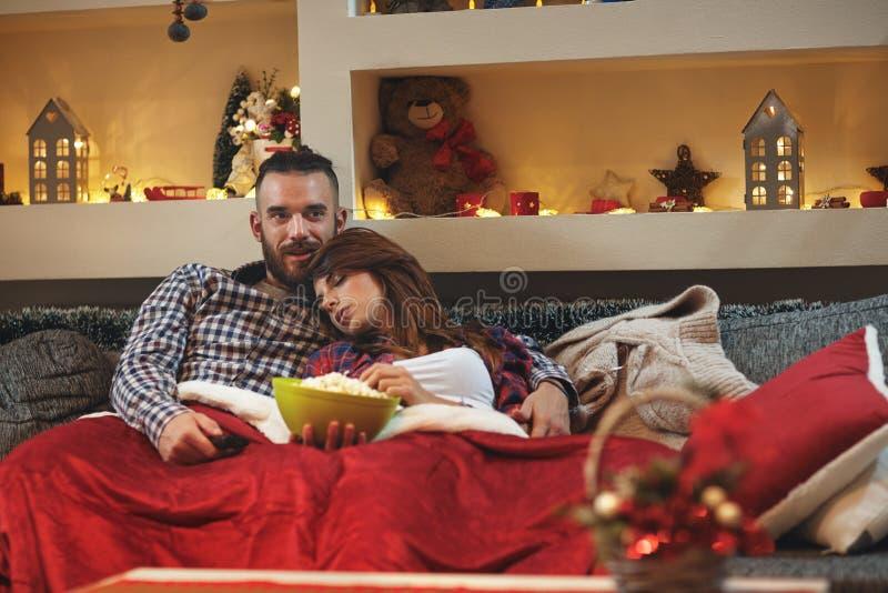 De vrouwendaling in slaap bij de mens ` s omhelst terwijl het letten van op TV royalty-vrije stock afbeeldingen