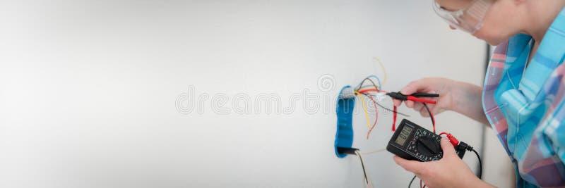 De vrouwenelektricien gebruikt digitale meter om het voltage bij de machtsafzet te meten stock fotografie