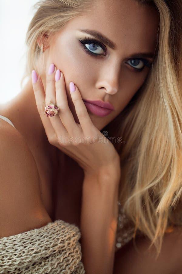 De vrouwengezicht van de schoonheidsmannequin Portret met roze Roze bloem Mooie Blondevrouw met Perfecte Make-up en Manicure royalty-vrije stock fotografie