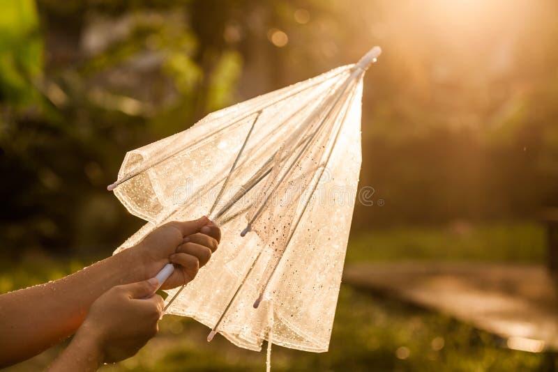 De vrouwenhand dicht en houdt een paraplu na regen stock afbeelding