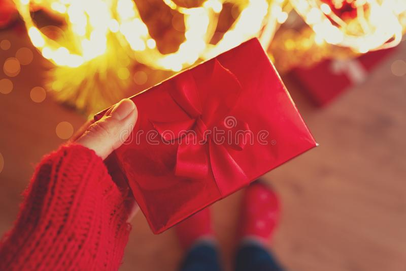De vrouwenhand die de rode doos van de Kerstmisgift houdt verpakte rood lint tegen achtergrond van Kerstboomlichten Kerstmis of n royalty-vrije stock afbeelding