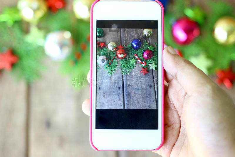 De vrouwenhand houdt de telefoon om foto's van Kerstmisdecoratie te nemen stock fotografie