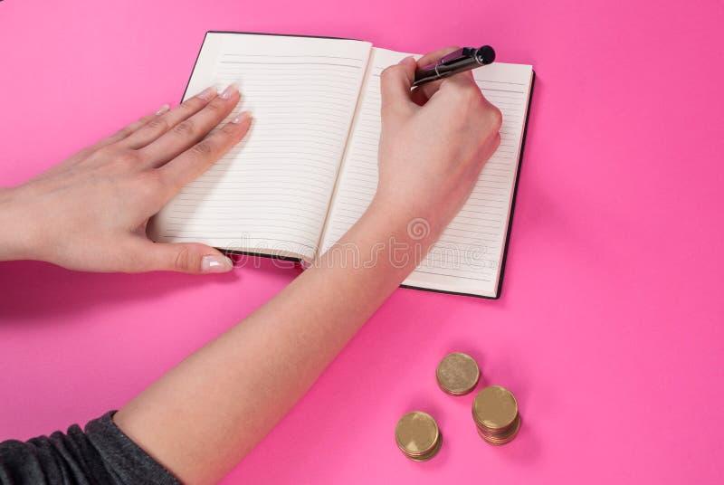 De vrouwenhand houdt een pen in hand en schreef naast het muntstuk op roze achtergrond stock fotografie