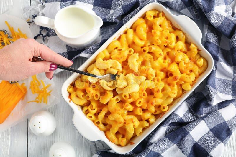 De vrouwenhand houdt een vork met MAC & kaas stock foto's