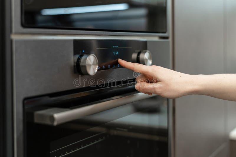 De vrouwenhand kiest programma over elektronische controlebord ingebouwde oven stock fotografie