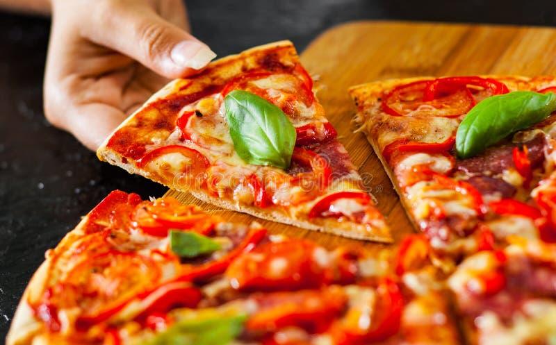 De vrouwenhand neemt een stuk van Pizza met Mozarellakaas, Ham, Tomaten, salami, peper, pepperonis, Kruiden en Vers Basilicum royalty-vrije stock foto