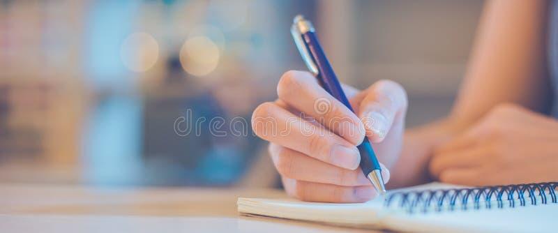 De vrouwenhand schrijft op een blocnote met een pen in bureau De banner van het Web stock fotografie