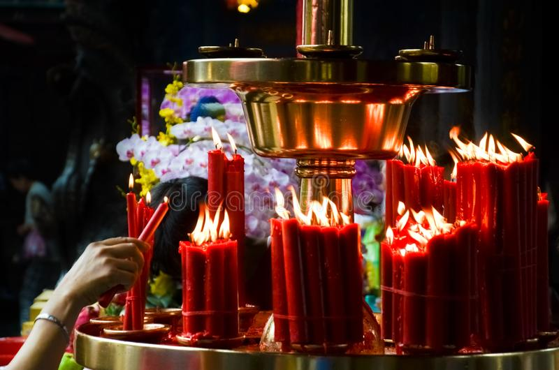 De vrouwenhand steekt rode kaarsen in Boeddhistische tempel, Taiwan, China aan Godsdienstig concept, spiritualiteit, geloof, God  royalty-vrije stock afbeeldingen