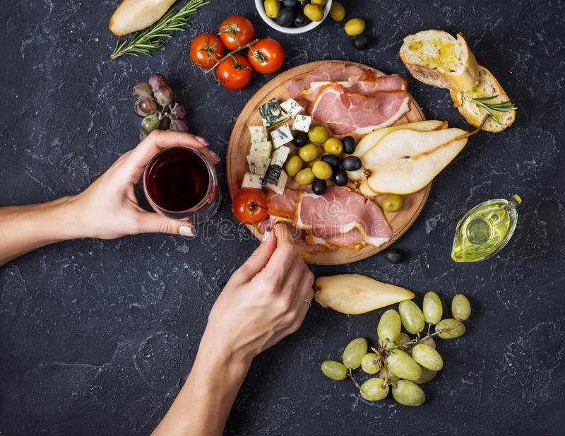 De vrouwenhanden houden een glas wijn Voorgerecht, Italiaanse antipasto, ham, olijven, kaas, brood, druiven, peer op donkere stee royalty-vrije stock foto