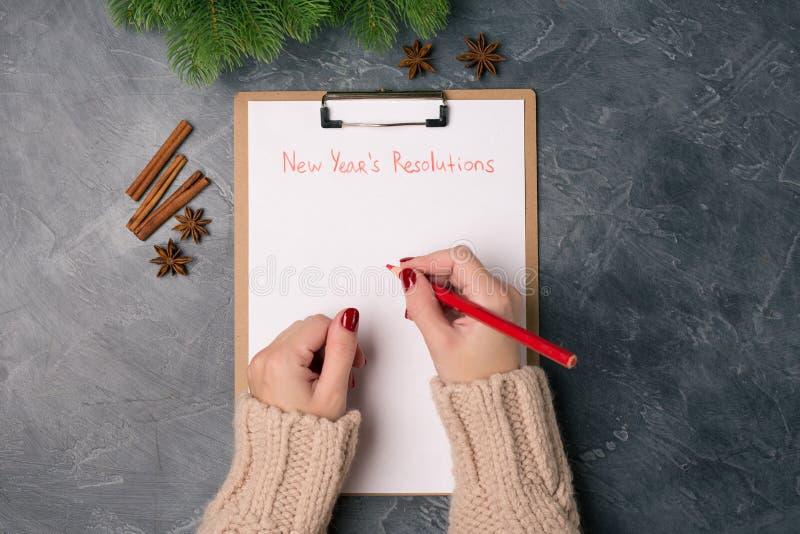 De vrouwenhanden klaar om de resoluties te schrijven van het nieuwe jaar over spatie listFlat leggen Hoogste mening Het concept v stock fotografie