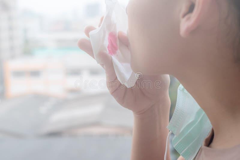 De vrouwenhanden of de vrouwelijke handen die een beschermend masker en een servet met bloed wegens luchtvervuiling in de stad ho royalty-vrije stock foto's