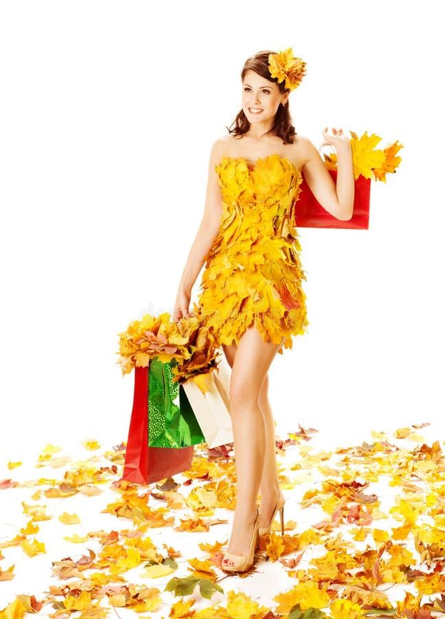 De vrouwenherfst die in kleding van esdoornbladeren winkelen over wit royalty-vrije stock foto