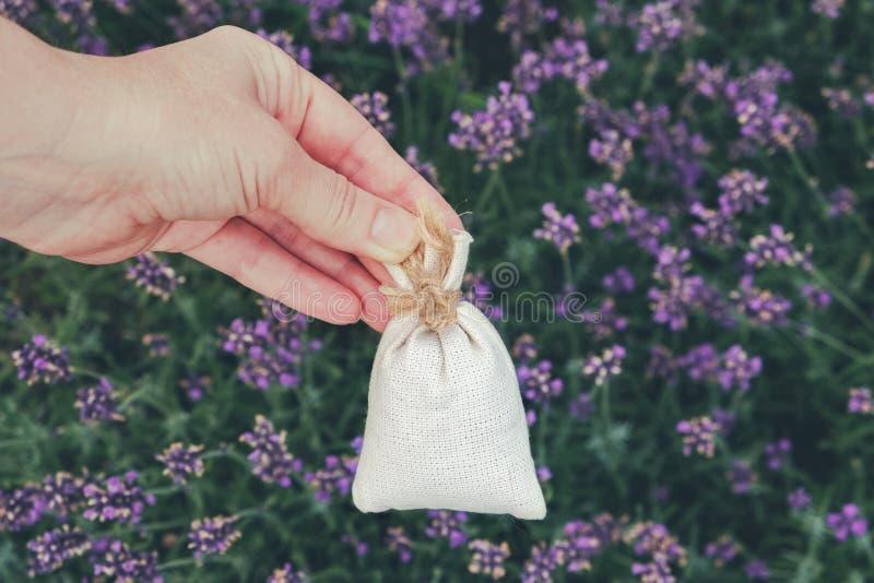 De vrouwenholding in haar overhandigt een sachet met droge lavendel wordt gevuld die stock afbeelding