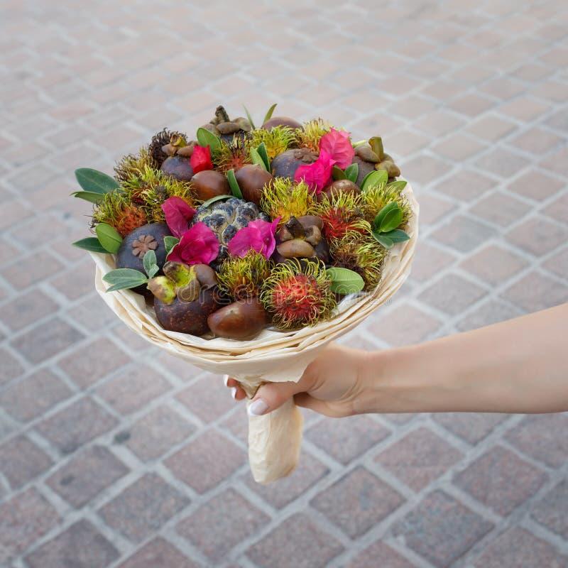 De vrouwenholding in haar overhandigt de unieke gift in de vorm van een boeket van exotische vruchten stock afbeelding