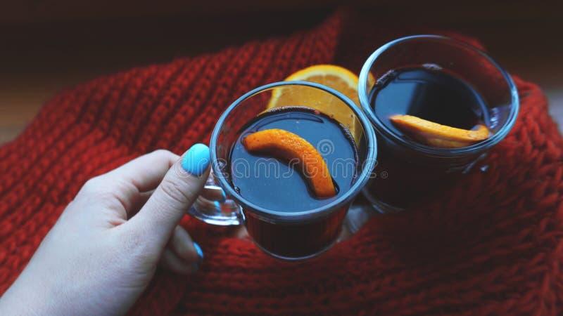 De vrouwenholding overwoog wijn met kruiden en omhoog sluiten de citrusvruchten in haar hand, stock foto