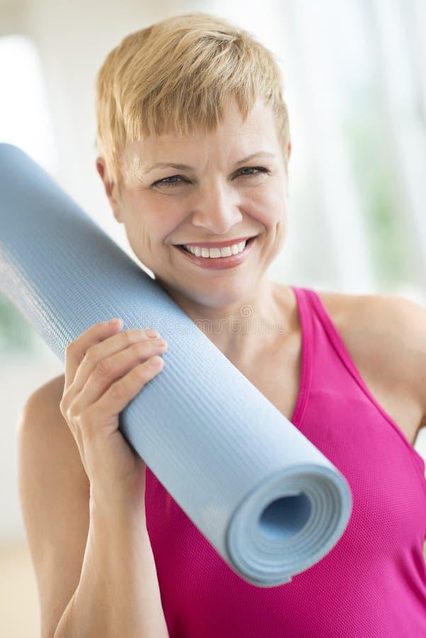 De vrouwenholding rolde Oefening Mat At Gym op royalty-vrije stock afbeelding