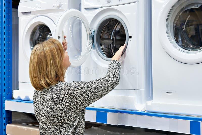 De vrouwenhuisvrouw kiest wasmachine in winkel van huis applianc stock fotografie