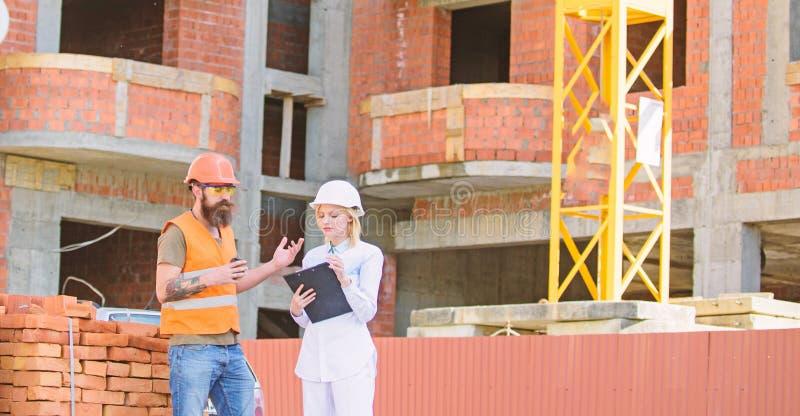 De de vrouweningenieur en bouwer communiceren bij bouwwerf Communicatie van het bouwteam concept verhoudingen stock afbeeldingen