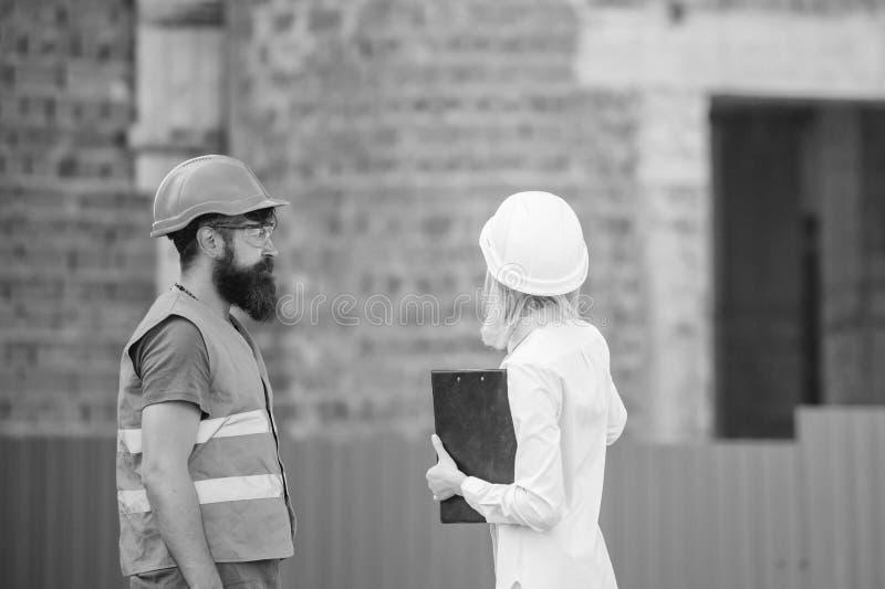 De vrouweningenieur en de gebaarde brutale bouwer bespreken bouwvooruitgang Bespreek vooruitgangsplan Bouwnijverheid stock foto