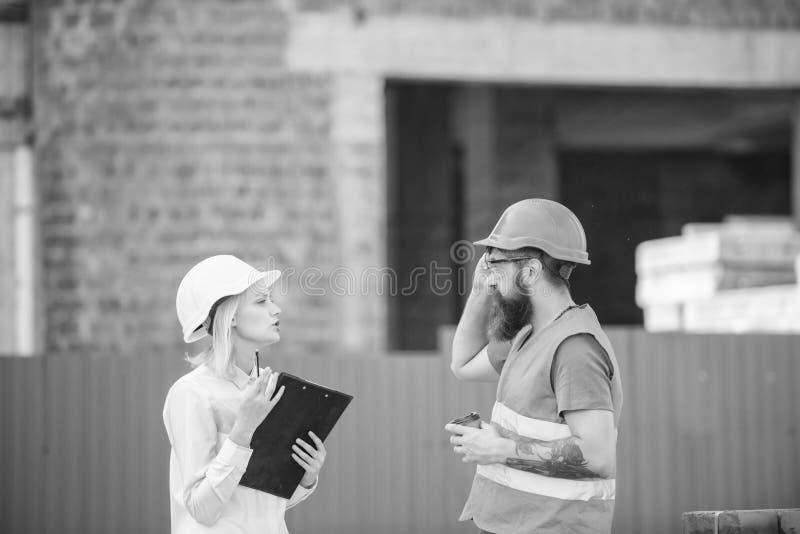 De vrouweningenieur en de gebaarde brutale bouwer bespreken bouwvooruitgang huis pictogram dat van sleutels, op bakstenen muurach royalty-vrije stock afbeelding