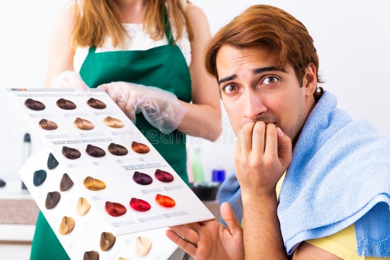 De vrouwenkapper die kleurstof toepassen op man haar stock afbeelding