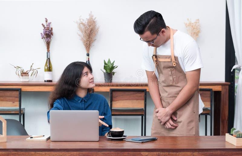 De vrouwenklant die van Azië aan kelner over voedsel in koffie onderzoek klagen royalty-vrije stock afbeelding