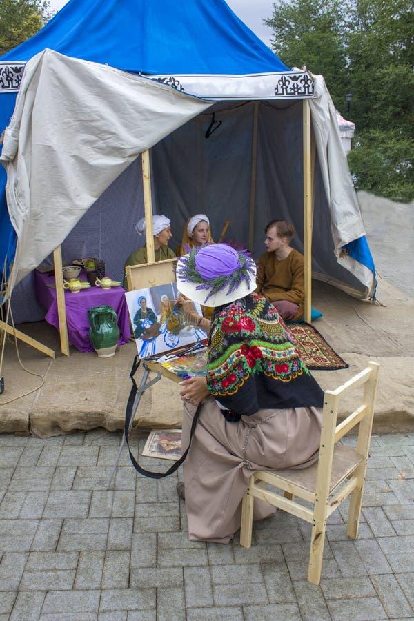 De vrouwenkunstenaar in een lavendelhoed trekt op canvasmensen die in een oude blauwe tent zitten festival Vremena i royalty-vrije stock foto's