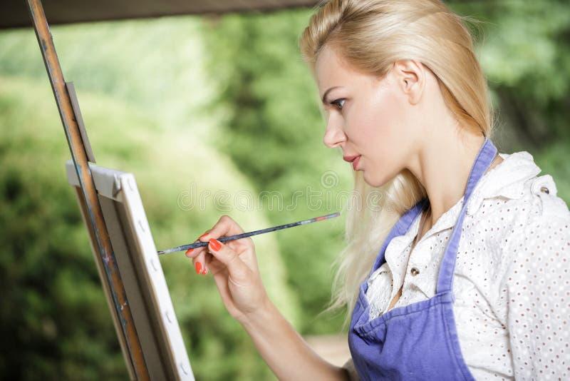 De vrouwenkunstenaar met een borstel in haar hand trekt op canvas stock foto