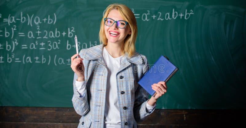 De vrouwenleraar met boek voor bord denkt over het werk Onderwijs de strategieën van de kennisverwerking kennis stock afbeelding