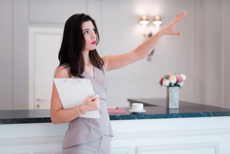 De vrouwenmakelaar in onroerend goed stelt voor om vlak of flat te bezoeken De agent toont met hand iets flat stock foto