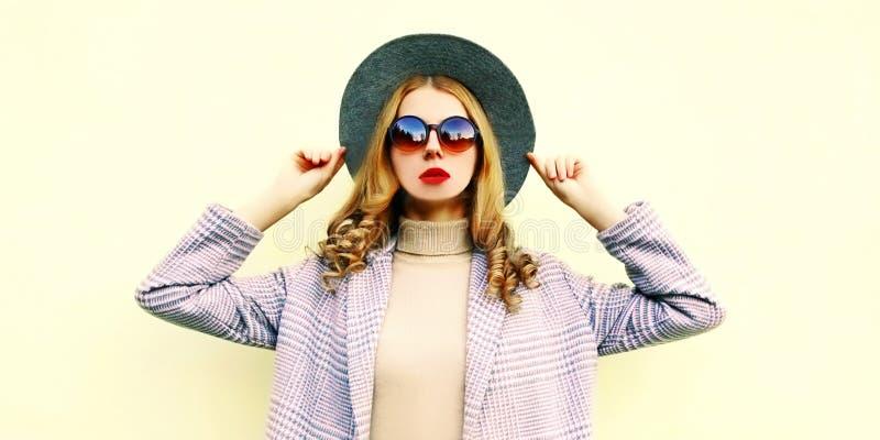 De vrouwenmodel van het portretclose-up in roze laag, het ronde hoed stellen op achtergrond stock afbeelding