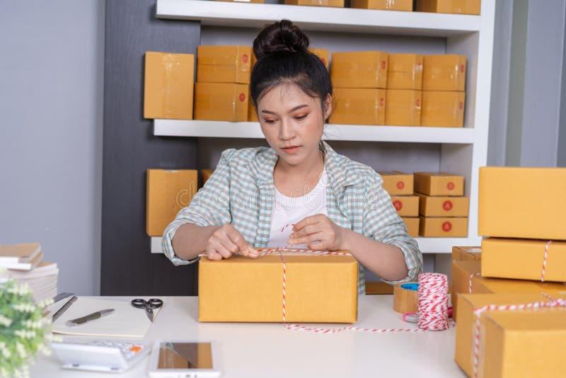 De vrouwenondernemer bindt kabels en pakt producten in parce in stock foto