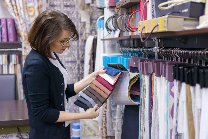De vrouwenontwerper, decorateur kiest stoffen voor gordijnen, hoofdkussens, bordurende stoffen, tapijten in de textielshowruimte royalty-vrije stock fotografie