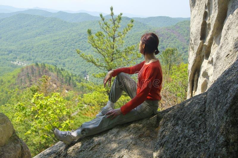 De vrouwenreiziger zit en bekijkt de vallei royalty-vrije stock fotografie