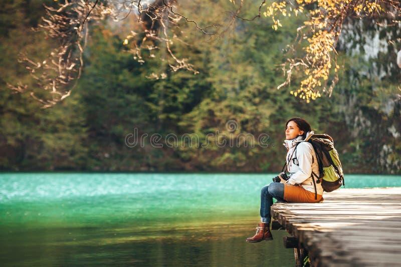 De vrouwenreiziger zit op houten brug op bergmeer bij zonnige aut stock afbeelding
