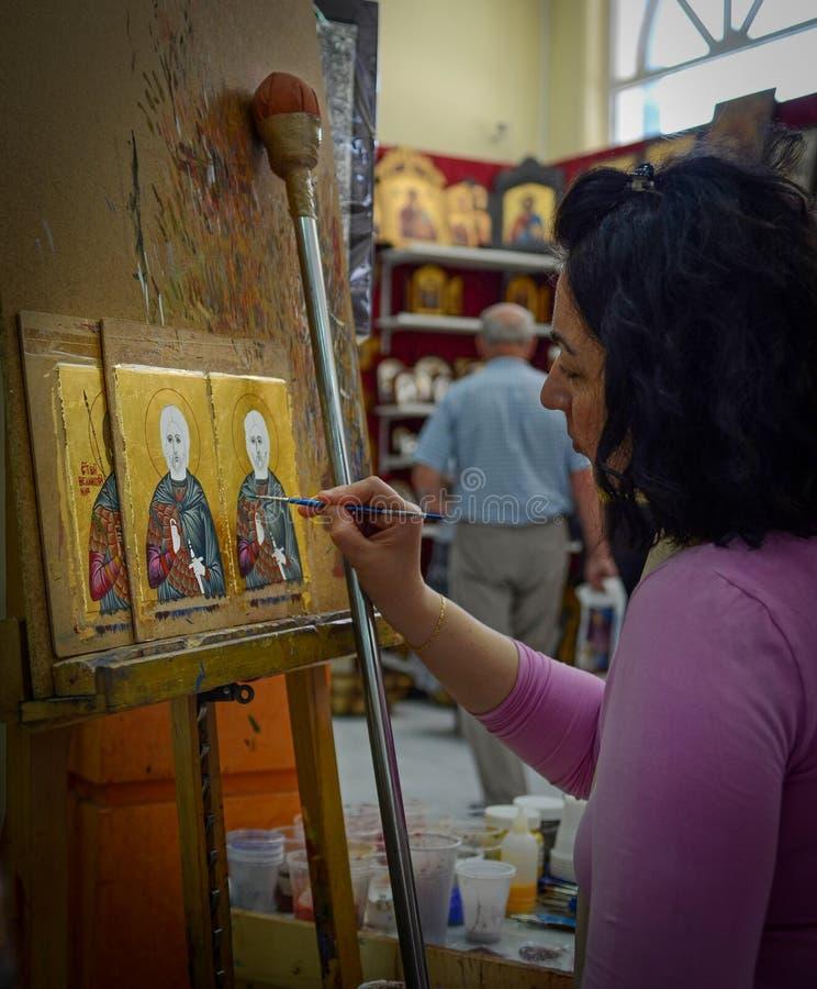 De vrouwenschilder schildert pictogrammen in pictogramwinkel royalty-vrije stock fotografie