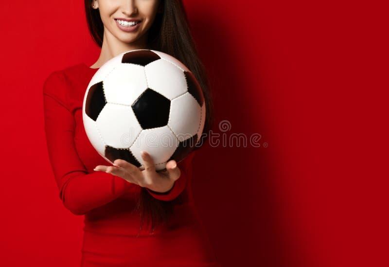 De vrouwenspeler die van de ventilatorsport in de rode eenvormige bal van het greepvoetbal gelukkige omhooggaand met de ruimte va royalty-vrije stock foto's