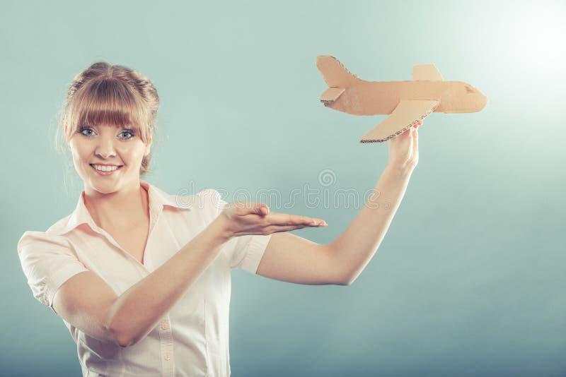 De vrouwenstewardess nodigt om te reizen uit houdt vliegtuig royalty-vrije stock afbeelding
