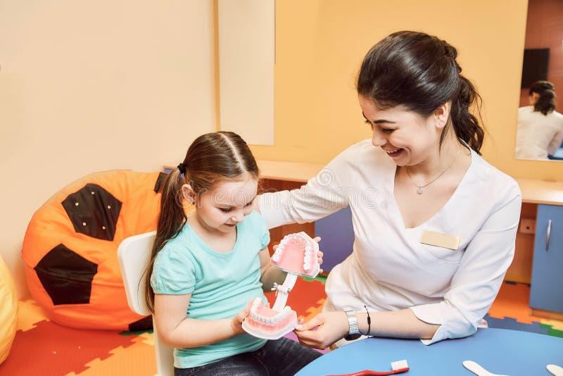De vrouwentandarts onderwijst meisje om haar tanden te borstelen stock afbeeldingen