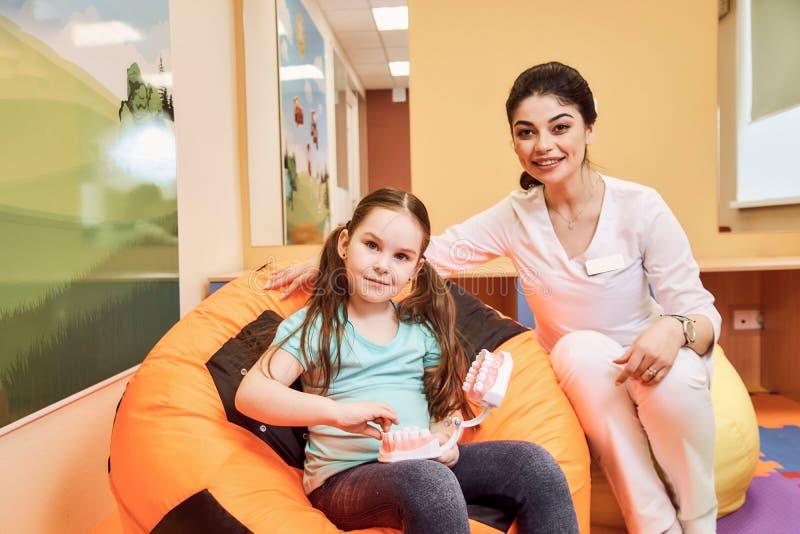 De vrouwentandarts onderwijst meisje om haar tanden te borstelen royalty-vrije stock foto's