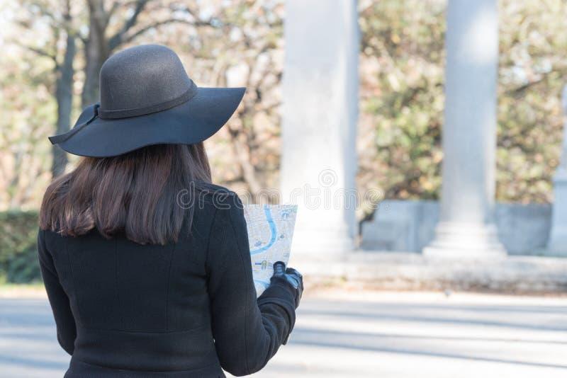 De vrouwentoerist bekijkt de kaart op de straat stock foto