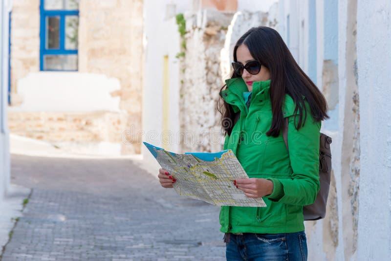 De vrouwentoerist bekijkt de kaart op de straat royalty-vrije stock fotografie