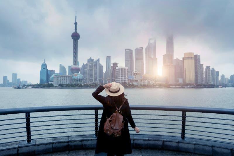 De vrouwentoerist is geniet van lettend op van de de bedrijfs stadshorizon van de oriëntatiepuntmening district stock foto