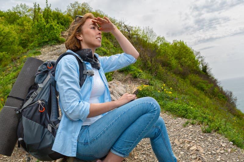De vrouwentoerist ging zitten om bovenop de berg te rusten en onderzoekt de afstand stock foto's