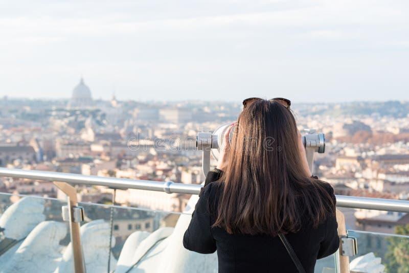 De vrouwentoerist kijkt door verrekijkers op stad Rome stock afbeeldingen