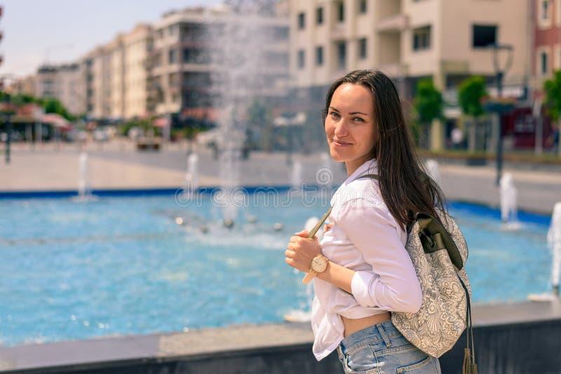 De vrouwentoerist loopt rond de stad met rugzak op de achtergrond van de fontein royalty-vrije stock foto's